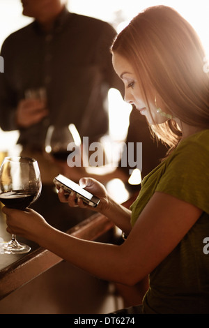 Businesswoman looking at cellphone in a wine bar - Stock Photo