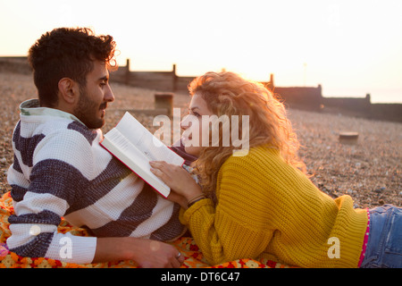 Young couple lying on beach, woman reading book - Stock Photo