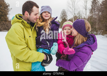 Mother and father carrying daughters in snow - Stock Photo