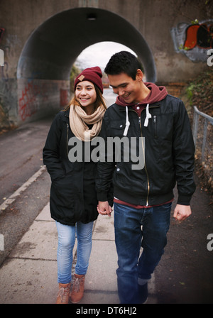 Loving young couple walking on a street smiling. Mixed race couple walking on sidewalk. - Stock Photo