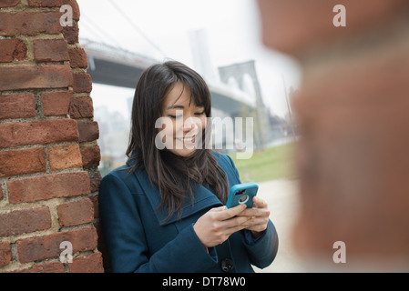 New York city. The Brooklyn Bridge crossing over the East River. A woman leaning against a brick wall, checking - Stock Photo