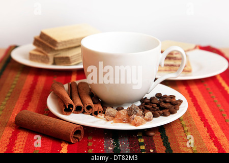 Cinnamon sticks with white empty cup on red background - Stock Photo