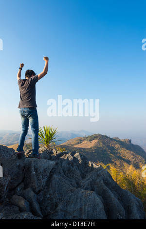 man standing on stone top of high mountain - Stock Photo