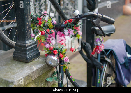 Old Fashioned or Vintage Bike or Bicycle decorated with Pink Flowers near Canal House in Amsterdam - Stock Photo