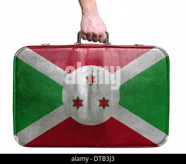 Tourist hand holding vintage leather travel bag with flag of Burundi - Stock Photo