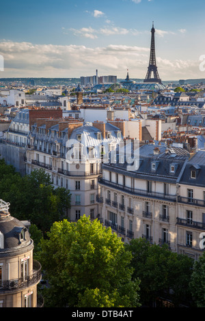 Evening sunlight over the buildings of Paris France with the Eiffel Tower beyond, Paris, Ile-de-France, France - Stock Photo