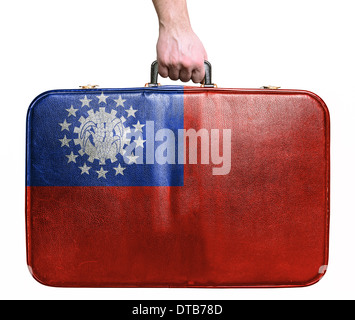 Tourist hand holding vintage leather travel bag with flag of Myanmar - Stock Photo