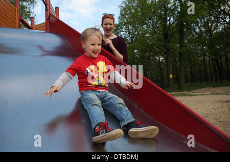Berlin, Germany , a small child sliding down a slide - Stock Photo
