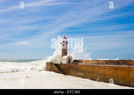 Waves over lighthouse in Porto on bright sunny day - Stock Photo