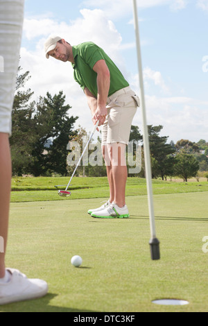 Young male golfer putting on golf green - Stock Photo