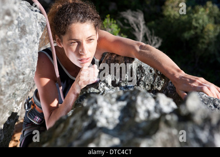 Young female rock climber moving up rock face - Stock Photo