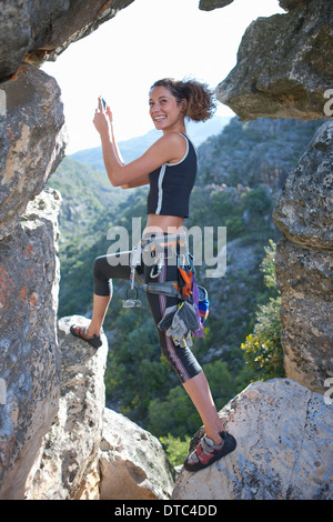 Young female rock climber taking selfie on smartphone - Stock Photo