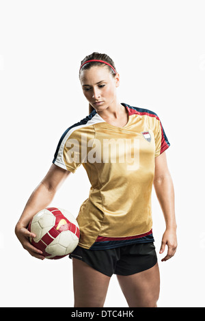 Studio shot of young female soccer player holding ball - Stock Photo