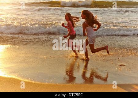 Two girls running along beach at sunset - Stock Photo