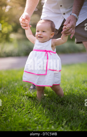 Grandfather helping granddaughter to walk - Stock Photo
