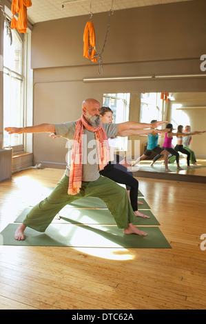 People doing warrior pose in yoga class - Stock Photo
