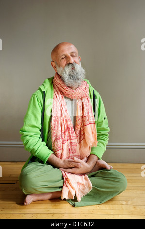 Portrait of senior man sitting in lotus position on floor - Stock Photo
