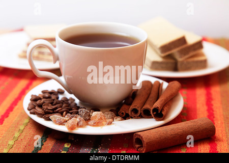 Cinnamon sticks with white cup on red background - Stock Photo