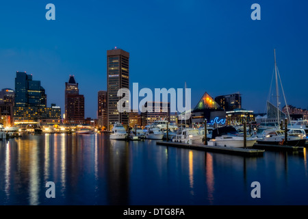 Baltimore Inner Harbor Skyline and refections in the water during the twilight hour after sunset. - Stock Photo