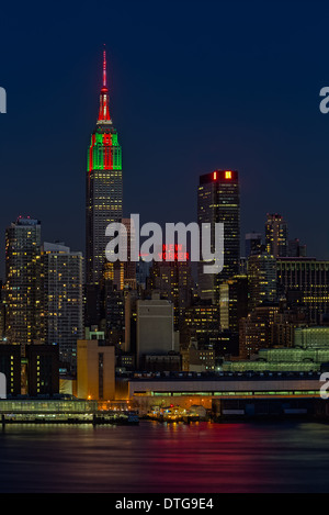 The Empire State Building in the New York City Skyline, illuminated in red, green and white in celebration of Christmas. - Stock Photo
