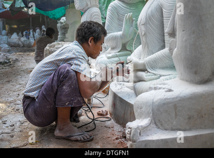 Young man carving an image of Buddha marble in a workshop in Mandalay, Myanmar - Stock Photo