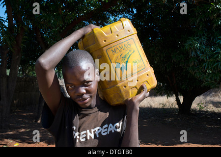 One of the inhabitants of Mukuni Village bringing a water jerican. He's wearing a Greenpeace t-shirt. Mukuni Village - Stock Photo