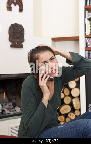 young woman at home at fireplace talking on mobile phone (model-released) - Stock Photo