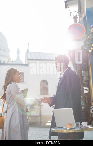 Business people shaking hands at sidewalk cafe, Paris, France - Stock Photo