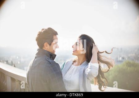 Couple hugging on urban balcony - Stock Photo