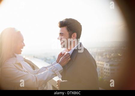 Woman holding boyfriend's collar on urban balcony - Stock Photo