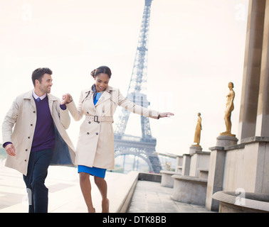 Couple walking in front of Eiffel Tower, Paris, France - Stock Photo