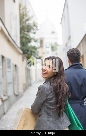 Couple carrying shopping bags in street near Sacre Coeur Basilica, Paris, France - Stock Photo