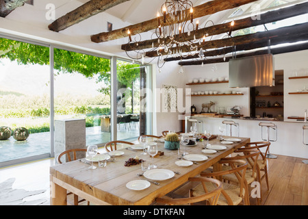 Chandelier over dining table in modern house - Stock Photo