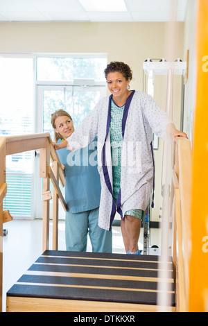Female Patient Being Assisted By Nurse - Stock Photo