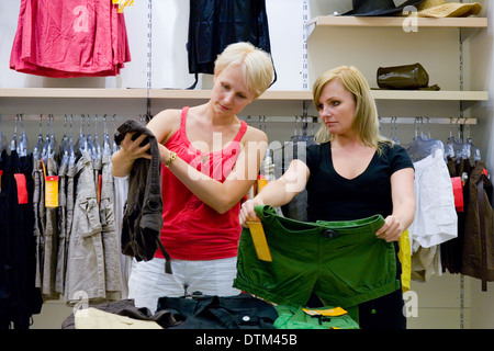 Two women comparing different clothes in shop. Retail store, fashion. - Stock Photo