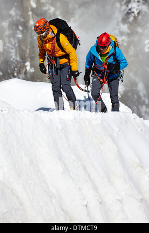 Two climbers returning to the Aiguille du Midi station after climbing Mont Blanc in the French Alps above Chamonix. - Stock Photo