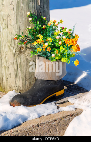 Silk flower in a rubber boot amongst the snow. - Stock Photo
