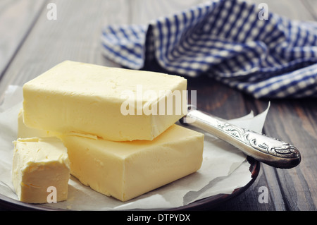 Fresh butter on wooden cutting board with knife closeup - Stock Photo