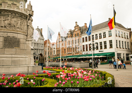 Markt in central Bruges Belgium features tulips blooming in Spring - Stock Photo