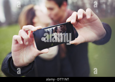 Loving young couple photographing themselves with a mobile phone while kissing at the park. Focus on smart phone. - Stock Photo