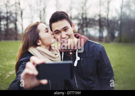 Pretty young girl kissing her boyfriend on cheeks while taking self portrait with a mobile phone. Mixed race couple - Stock Photo