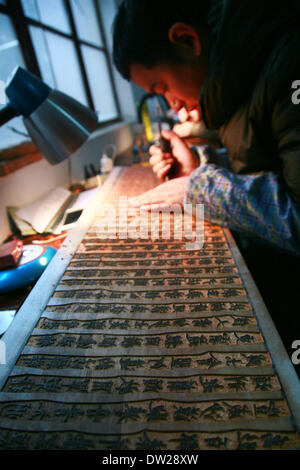 Yangzhou, China's Jiangsu Province. 25th Feb, 2014. A worker does the carving at the Guangling Ancient Books Printing - Stock Photo