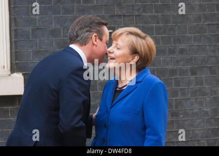 London, UK. 27th February 2014. British Prime Minister  David Cameron greets German Chancellor Angela Merkel as - Stock Photo