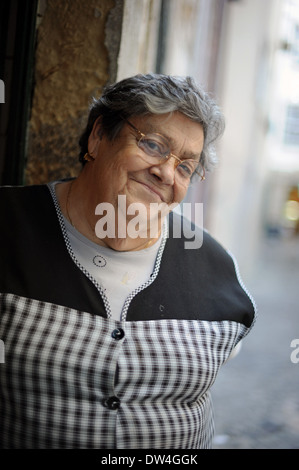 An elderly women walks in Alfama, the oldest district in Lisbon, Portugal. - Stock Photo