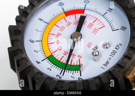 A compressor pressure gauge on a white background - Stock Photo