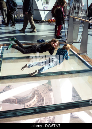 Two young girls lie on the glass floor of the Spinnaker Tower, Portsmouth, England - Stock Photo