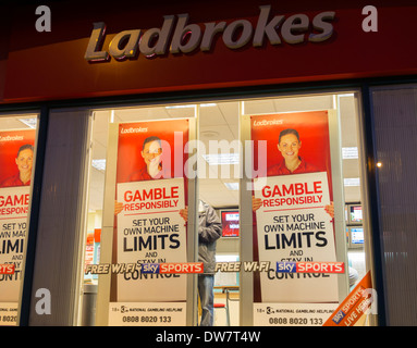 Gamble responsibly posters showing national gambling helpline number in Ladbrokes Bookmakers. - Stock Photo