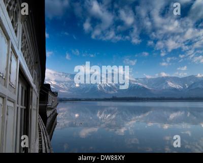 India, Kashmir, Srinagar, winter snow covered Zabarwan mountains reflected in Dal Lake at dawn - Stock Photo