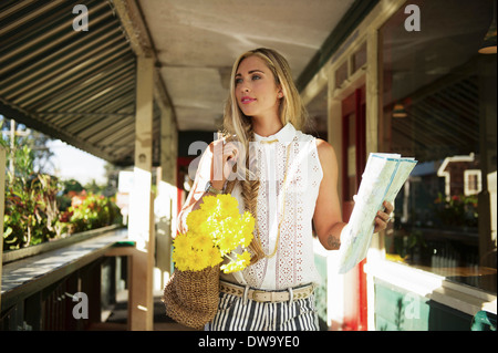 Young woman with map in verandah - Stock Photo