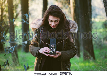Young woman with camera in the woods - Stock Photo